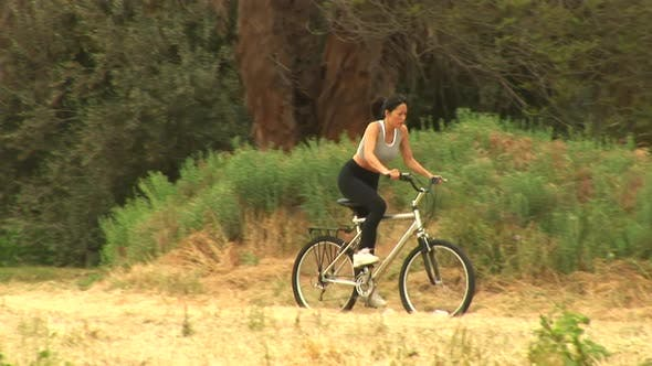 Young woman riding a bicycle in rural setting