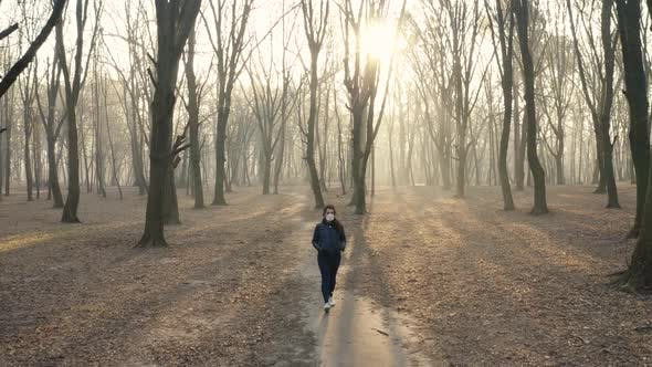 Woman in Face Mask Is Walking in the Woods. Toxic Smoke or Fog in the Forest at Sunset. Ecology