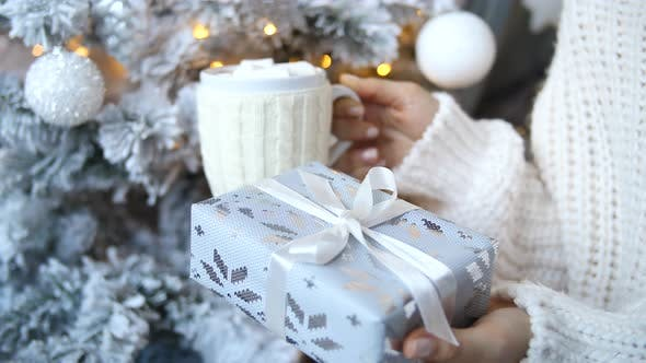 Thumbnail for Christmas. Close-Up Of Female Hands Holds Xmas Present And Cup Of Hot Chocolate.