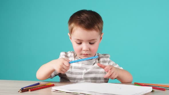 Thumbnail for Young Talented Boy Draws a Pencil Drawing in Album on Blue Background.
