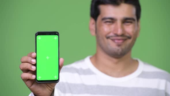 Young Handsome Persian Man Showing Phone