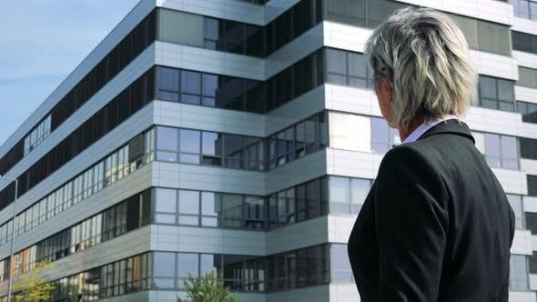 Thumbnail for Business Middle Age Frau schaut sich um (Shot from Side) - Firmengebäude im Hintergrund