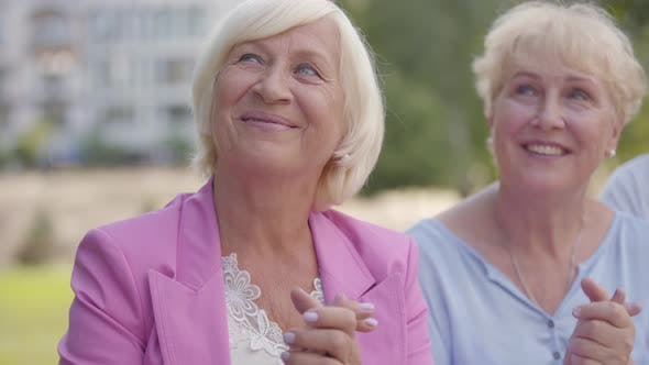 Zwei positive Senior Frauen klatschen ihre Hände und Blick auf etwas