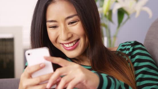 Thumbnail for Happy Japanese woman texting on smartphone