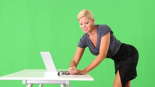 Provocative businesswoman standing by desk and typing