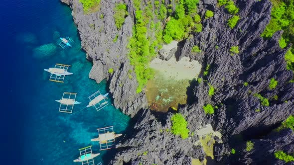 Thumbnail for Aerial Drone View of Swimmers Inside a Tiny Hidden Tropical Lagoon Surrounded By Cliffs