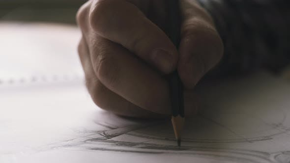 Designer Drawing Plans On Paper With Pencil