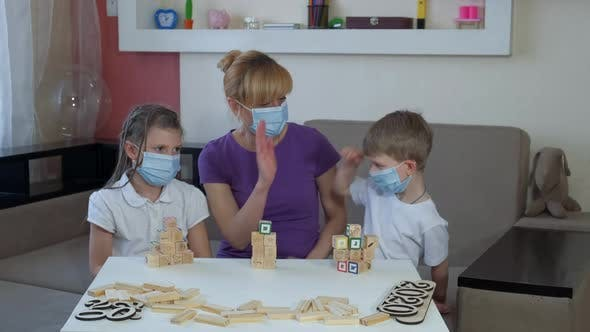 Mother Son and Daughter in Medical Masks Play Wooden Puzzles in the Room