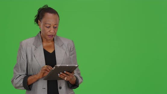 Thumbnail for A black businesswoman using a tablet turns to the camera and says hello on green screen