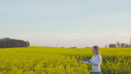 Thumbnail for Female Farmer Examining Oilseed Rape Field