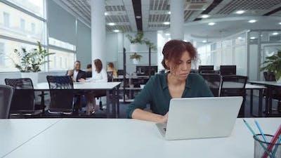 Black Woman Using Laptop in Coworking Space