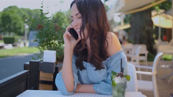Thumbnail for Pretty Brunette Woman Sitting in Outdoor Restaurant and Talking Her Mobile Phone