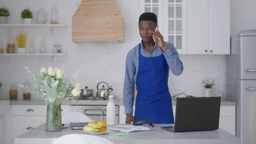 Serious Confident African American Man in Blue Apron Talking on the Phone Standing in Kitchen