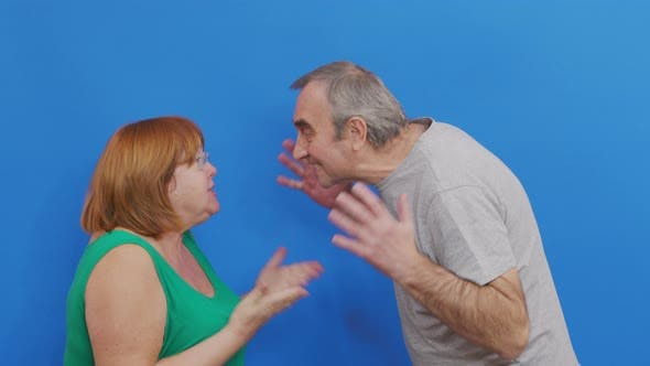 Couple Quarreling on Blue Background. Aged Couple Quarreling. Conflict, Negative Emotions.