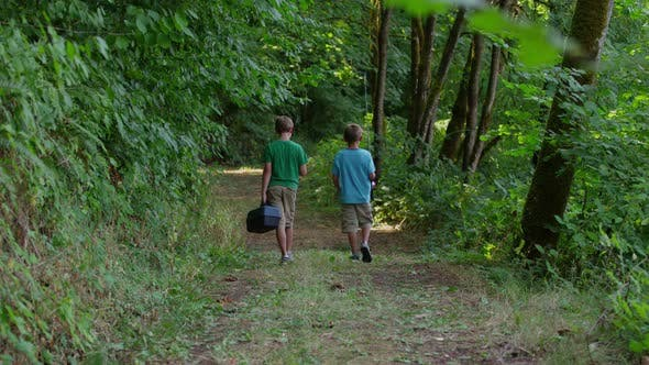 Two young boys walking to fishing hole