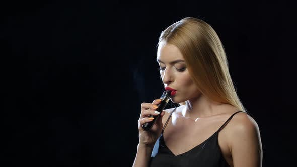 Girl Smiles, Inhales and Exhales the Smoke of an Electronic Cigarette. Black Background