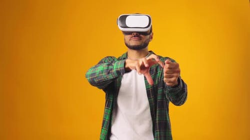 Casual African American Man Using VR Technology Wearing Headset Against Yellow Background