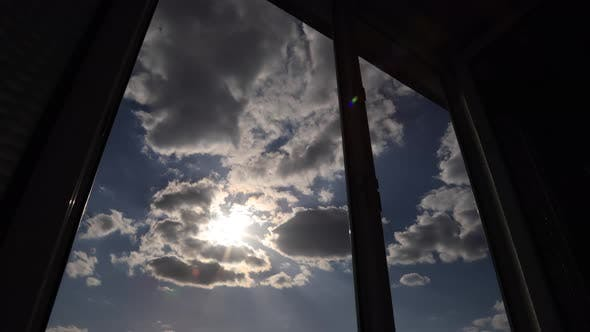 Amazing time lapse: the sun appears in window on the background with fluffy clouds
