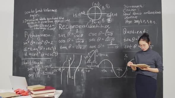 Female Asian Bachelor Reading Book at Blackboard