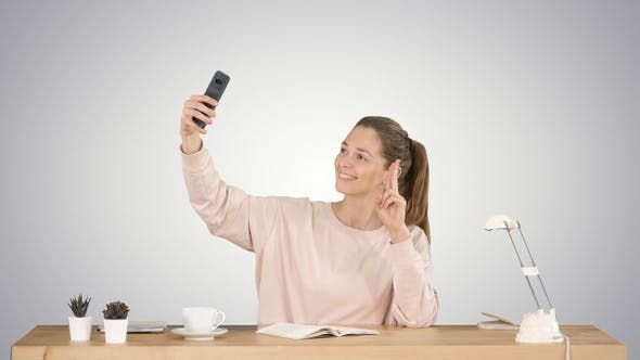 Cover Image for Beautiful woman taking a selfie with her cell phone sitting