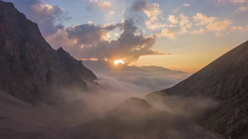 Mountains and Moving Clouds at Sunset. Aerial Hyper Lapse