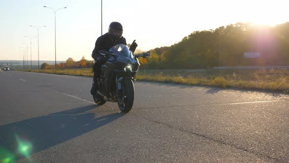 Young Man in Helmet Riding on Modern Sport Motorbike at Highway with Sun Flare at Background