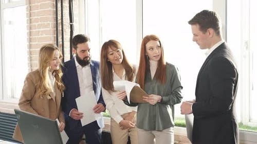 Redhaired Girl Boss Celebrates Company Success with Her Multirace Colleagues