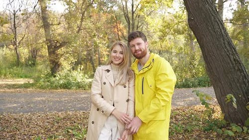 Young Couple in Love Stands in an Open Park, the Couple Is Happy Together, Smiling at the Camera on