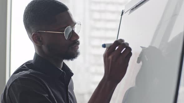 Concentrated African American Afro Black Male Manager in Glasses Writing Notes on White Board