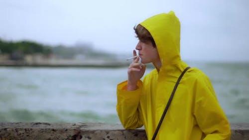 Teenager Smoking on Shore Looks Back Wind Slomo