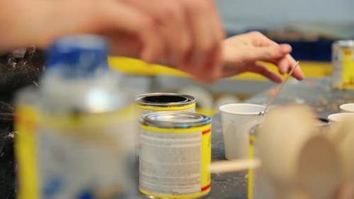 Female Artist Mix Paint From Can in Workshop