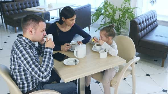 Thumbnail for Father Talking To Phone While Sitting with His Wife and Daughter in Cafe or Restaurant