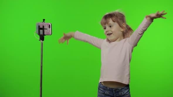 Girl Child Makes Selfie Vlog, Blogging, Video Call on Mobile Phone Using Monopod