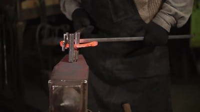 Close Up Shot of the Man's Hands, Who Bends the Steel on the Anvil in an Arc