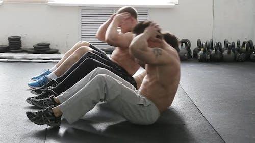 Schweres Crossfit-Workout. Gruppe von Sportmann-Sit-ups. Athleten trainieren im Fitnessstudio.