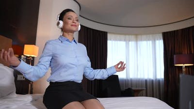 Female Meditating at Laptop Sitting on Hotel Bed