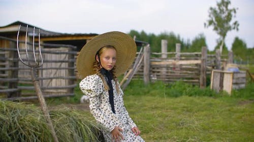 Rustic Girl in Vintage Dress and Hat on Haystack and Pitchfork Background in Countryside
