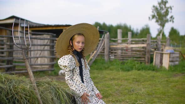 Thumbnail for Rustic Girl in Vintage Dress and Hat on Haystack and Pitchfork Background in Countryside