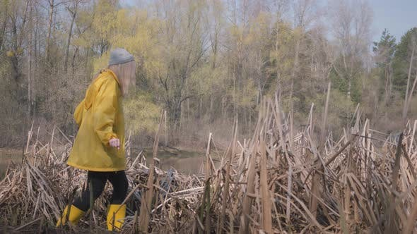 Thumbnail for Body of Human Walking Carefully in Swamp in Yellow Boots and Coat