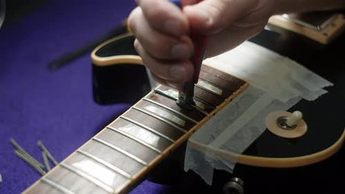 Refretting the Guitar Luthier Replaces Frets on the Electric Guitar Musical Instruments Repair Shop