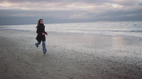 Thumbnail for Redheaded Teenage Girl In Black Waving On Beach