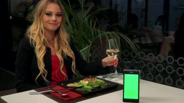 Thumbnail for A Woman Sits at a Table in a Restaurant, Smiles at the Camera - a Smartphone with a Green Screen
