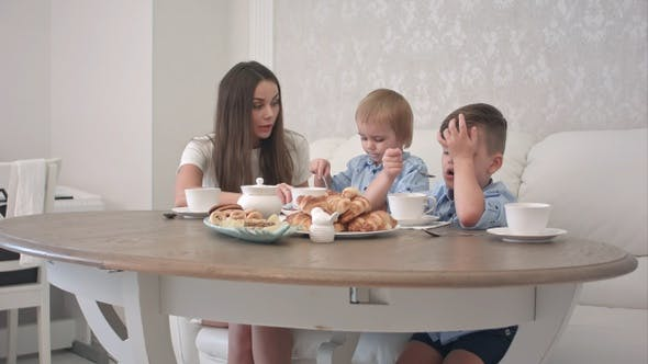 Thumbnail for Young mother attending to her little boys having tea at home