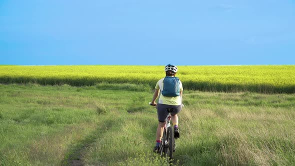 Woman Cyclist Moving On Bike On Countryside