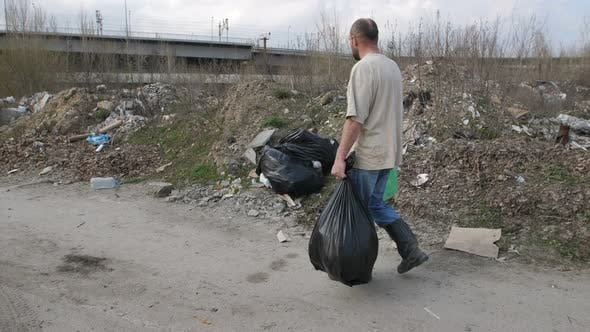 Thumbnail for View of Man Looking for Plastic at Landfill