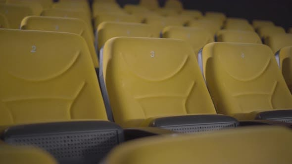Thumbnail for Empty Yellow Cinema Chairs with No People on Covid-19 Lockdown. Camera Moves Along Row of