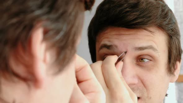 Thumbnail for Young Man Plucking His Eyebrows with Tweezers and and Winces From the Pain. Styling Eyebrows.