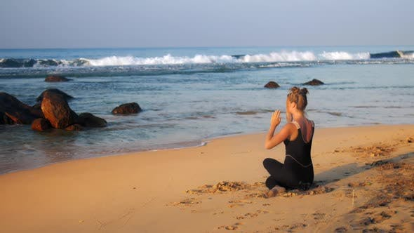 Thumbnail for Young Blond Woman in Black Tracksuit Meditates in Yoga Pose