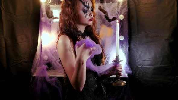Girl with Halloween Makeup Approaches the Camera Holding a Burning Candle in Her Hand.