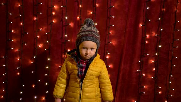 Thumbnail for Young boy posing serious in front of lights wall at Christmas market.